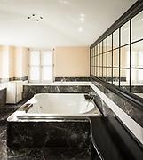Bathroom with black marble tiles and big bathtub