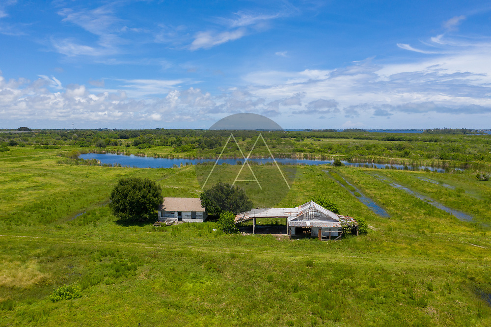 Aerial view of an abandoned farm house near Old Dixie Highway with a lake in background, St. Lucie County, Florida, United States.