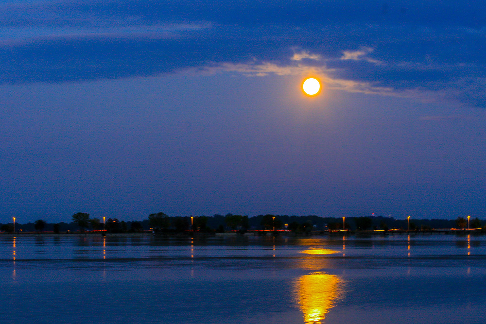 Supermoon casts a splash of gold on blue Monona Bay before slipping behind the clouds. John Nolan Drive visible on the horizon. Photo taken September 28, 2015.