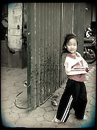 Young girl stands beside a corrugated metal gate, Hanoi, Vietnam, Southeast Asia