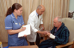 Male doctor attending to elderly man with young female nurse taking notes,