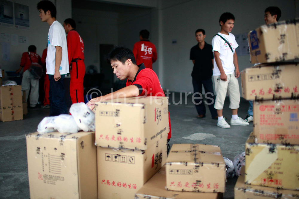 """Courriers sort and load shopping orders at one of the Yihaodian neighborhood distribution centers in Shanghai, China on 23 August, 2011. As online supermarkets is attracting a rapidly increasing number of young consumers, especially women, U.S. giant Walmart has acquired a minority stake in Yihaodian, or """"The Store"""", a young but very successful E-Commerce company that sells and delivers everything from food, daily household  items, electronics, and clothing."""