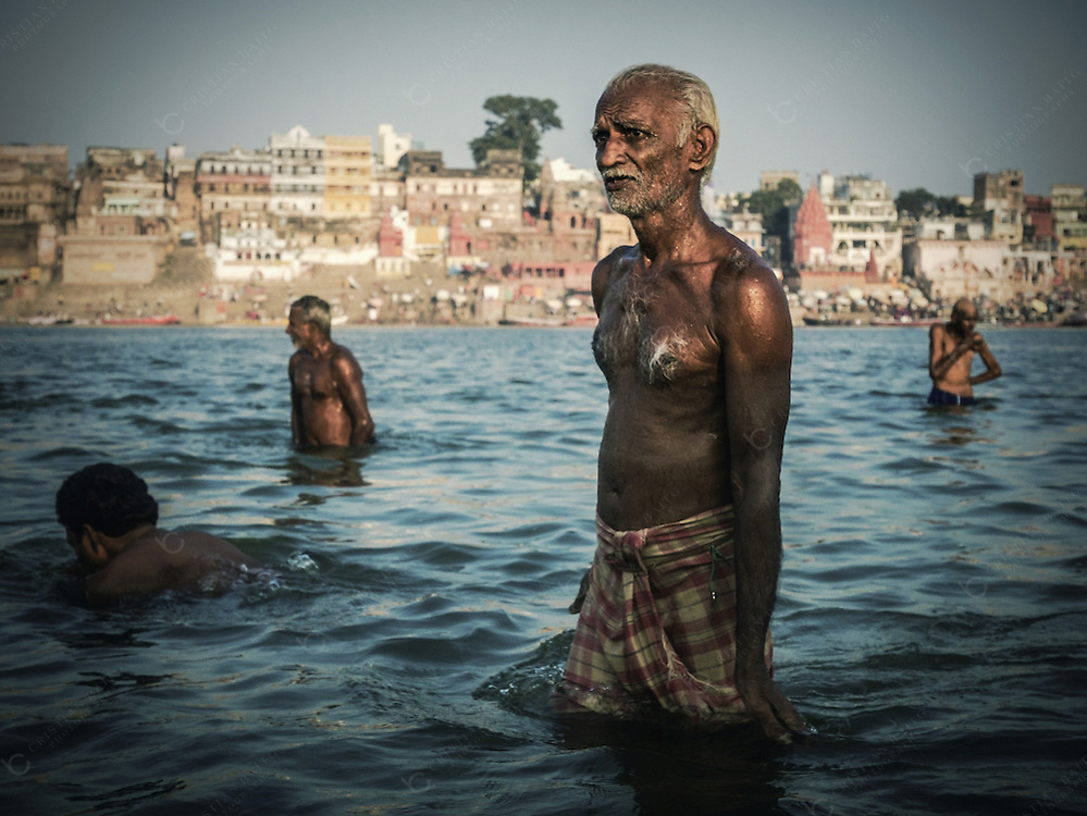 Varanasi, India - October 09, 2015 Pilgrims bathing at the Ganges river in Varnasi India. This is one of the oldest inhabited cities in the world and also the holiest of the seven sacred cities in Hinduism and Jainism and so the most important pilgrimage place for hindus.