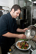 Restaurant's kitchen - cook makes a salmon and vegetable salad