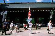 An old man in imperial navy uniform marches in front of the entrance gate to the  controversial Yasukuni Shrine carying a large old style Japanese flag during the celebrations of the end of the Pacific War. This shrine houses the spirits of Japan's war dead, including 14 Class A war criminals,and is a source of tension for Japanese neighbors, especially China and Korea who suffered badly at the hands of the Japanese Imperial forces before and during World War 2. Yasukuni Ginja Tokyo, Japan August 15th 2007