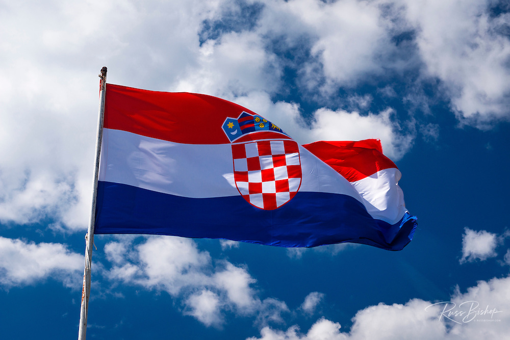 Croatian flag against blue sky and clouds, Ston, Croatia