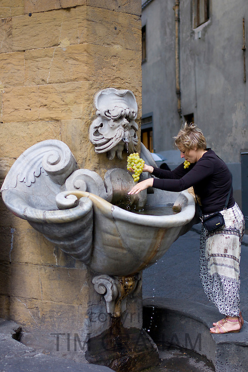 Woman washing grapes in water fountain in Florence,Tuscany, Italy