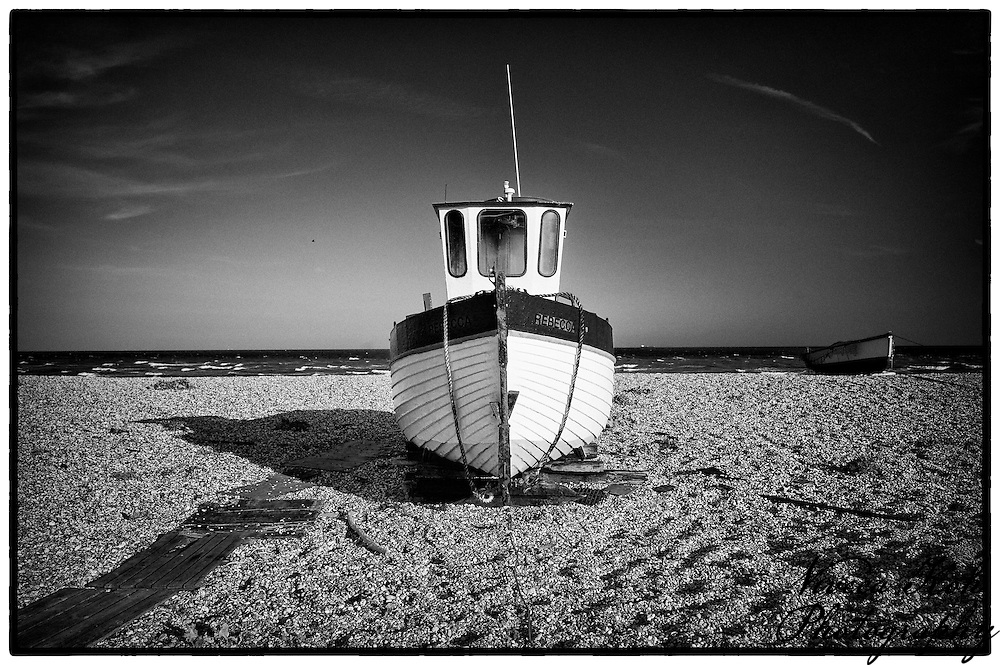 Wooden boat 'Rebecca' on the shingle beach at Dungeness, Kent, United Kingdom