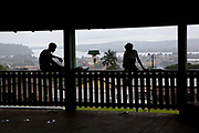 Teenagers sitting on a fence looking over the city of Altamira in silhouette and the river in the background