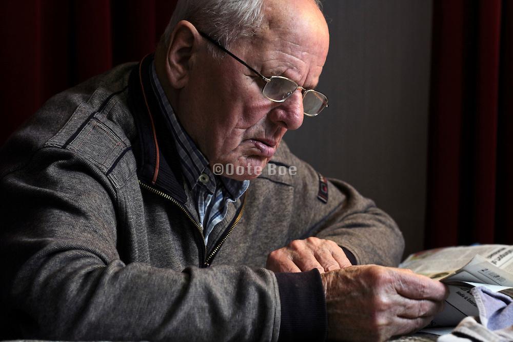 elderly 89 year old man reading the newspaper