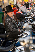 A biker wearing a top hat watches the parade of motorcycles down Main Street during the 74th Annual Daytona Bike Week March 8, 2015 in Daytona Beach, Florida. More than 500,000 bikers and spectators gather for the week long event, the largest motorcycle rally in America.