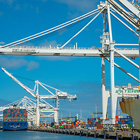 Giant cranes unload cargo from container ships at Oakland Harbor in San Francisco Bay, California.