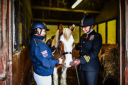 Royal Navy Officer Lieutenant Deni Milner, right, and Megan Conway, left, fuss over a horse named Bob the Cob at the Royal Navy and Royal Marines Riding Stables at Bickleigh Barracks, Plymouth, ahead of the first ever memorial service dedicated to horses killed or injured in conflict.
