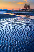 Ridges in the sand at Seattle's Discovery Park.  Low tide exposes a wide beach with West Point Lighthouse in the background.