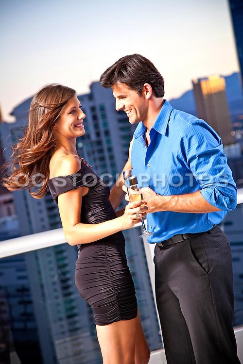 Romantic Couple Enjoying Drinks On A Balcony At Dusk