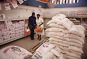 Poppy and Simon Qampie's main purchase at a supermarket is always corn meal, which they mix with water to form what is known as pap: hot cornmeal porridge. Published in Material World page 25..The Qampie family lives in a 400 square foot concrete block duplex house in the sprawling area of Southwest Township (called Soweto), outside Johannesburg (Joberg) South Africa.