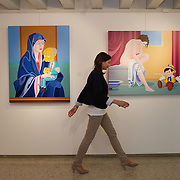 VENICE, ITALY - JUNE 01:  A member of staff walks in front og one of the works of  Giuseppe Veneziano at Galleria Contini on June 1, 2011 in Venice, Italy. Veneziano's controversial paintings portray  pop culture icons and historical figures.