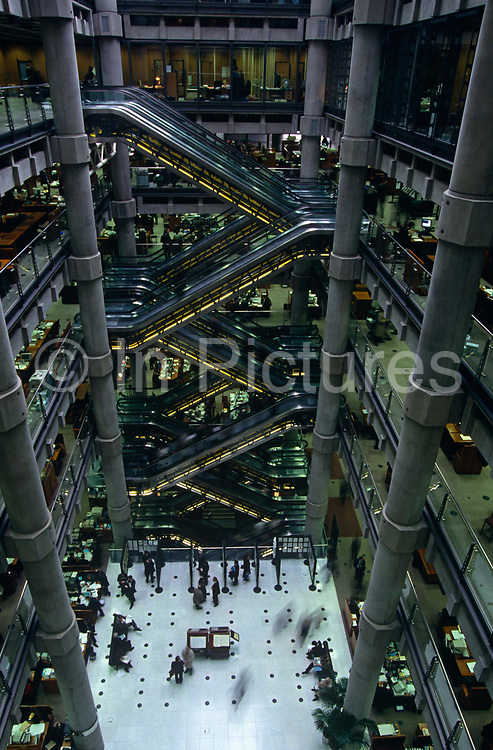 """From a high vantage point looking across the atrium of British architect Sir Richard Rogers' Lloyds building, we see the post-modern architecture of the insurance underwriters Lloyd's building, home of the insurance institution Lloyd's of London which is located at number 1, Lime Street, in the heart of the City of London. Lloyd's is a British insurance market. It serves as a meeting place where multiple financial backers or """"members"""", whether individuals (traditionally known as """"Names"""") or corporations, come together to pool and spread risk. Unlike most of its competitors in the reinsurance market and is neither a company nor a corporation. The Lloyds market began in Edward Lloyd's coffeehouse around 1688 and is today the world's leading insurance market providing specialist insurance services to businesses in over 200 countries and territories."""
