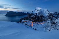 Streelights of Uttakleiv village shine below Himmeltindan mountain peaks in winter twilight, Vestvågøy, Lofoten Islands, Norway