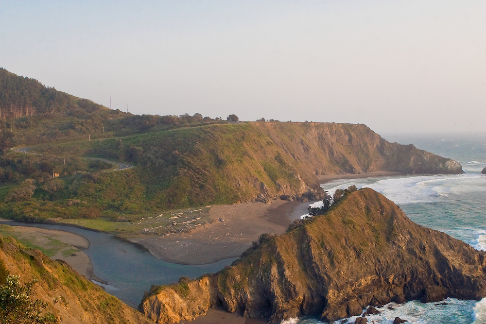 Two cliffs of a mountain jut into the ocean.  A river filters into the ocean.  A road runs up the side of one cliff.