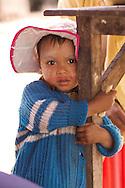 A Burmese child hugs a table in Myanmar.