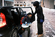 17 FEBRUARY 2021 - DES MOINES, IOWA: A student jumps out of their parents' car at Walnut Street School in downtown Des Moines. Des Moines Public Schools (DMPS) opened to in person education this week after teaching most of the 2020-2021 school year either remotely or with a hybrid/remote learning model. The district has ended its hybrid model. The Governor of Iowa has aggressively pushed schools to return to in person education, going so far as to threaten to withhold funds from districts that don't return to in person classes. DMPS, the largest school district in Iowa, has resisted the Governor's push because Polk County, IA, has been a Coronavirus/COVID-19 hotspot with positivity rates well above 10 percent. The district was recently able to vaccinate many teachers and positivity rates have fallen to 9 percent, making it safer to reopen schools.          PHOTO BY JACK KURTZ