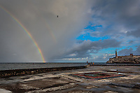 Fishermen plying their trade along the Malecón in Havana Cuba as a double rainbow descends into the Gulf of Mexico