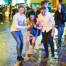 """© Licensed to London News Pictures . 23/12/2017. Manchester, UK. Two men help a woman cross Withy Grove , outside the Printworks . Revellers out in Manchester City Centre overnight during """" Mad Friday """" , named for being one of the busiest nights of the year for the emergency services in the UK . Photo credit: Joel Goodman/LNP"""