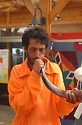 blowing the shofar, usually, the Shofar is used as a religious ritual instrument, in this case it is used for adding a beat to the rhythm of the music