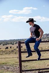 hot cowboy sitting on a fence