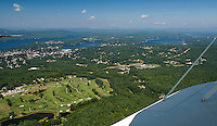 A beautiful day in the neighborhood as Lakes Biplane takes flight over Pheasant Ridge Golf Course with Winnisquam, Opechee and Paugus Bay on the horizon Thursday morning.  (Karen Bobotas/for the Laconia Daily Sun)