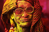 An old man covered in yellow and red color during the festival of colors, Holi, India.