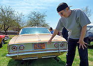 April 28, 2013 - Floral Park, New York, U.S. - DON PEZZOLLA points to the World's Fair 1965 license plate on the rear of his 1964 Chevy Corvair 140, at the Antique Auto Show, where New York Antique Auto Club members exhibited their cars on the farmhouse grounds of Queens County Farm Museum. Pezzolla explained that 1964 and 1965 were the only two years New York didn't require front license plates, because of the World's Fair in Queens.