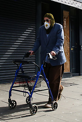 © Licensed to London News Pictures. 21/03/2020. London, UK. An elderly man wearing a face mask and supported by a frame, walks past a closed restaurant in Green Lanes, Haringey, north London. The closures follow Prime Minister, BORIS JOHNSON'S request that all restaurants, cafes and pubs should close until further notice as the Coronavirus impact worsens. Photo credit: Dinendra Haria/LNP