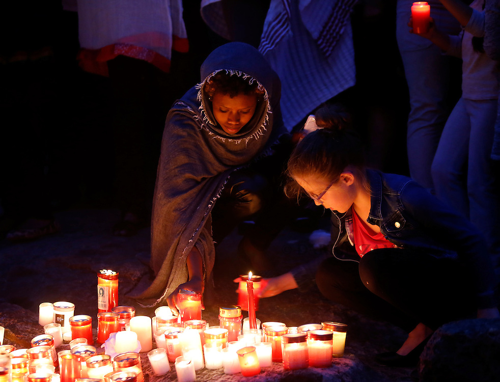 A migrant and a Maltese girl place candles on the shoreline rocks as they take part in a vigil to commemorate migrants who died at sea in Sliema, outside Valletta, April 22, 2015. European Union leaders who decided last year to halt the rescue of migrants trying to cross the Mediterranean will reverse their decision on Thursday at a summit hastily convened after nearly 2,000 people died at sea.  Public outrage over the deaths peaked this week after up to 900 migrants died last Sunday when their boat sank on its way to Europe from Libya. <br /> REUTERS/Darrin Zammit Lupi MALTA OUT. NO COMMERCIAL OR EDITORIAL SALES IN MALTA