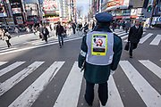 A man checks that people are not smoking in the street. Smoking restriction in public became a lot more restrictive  in 2013. many wards in Tokyo banned smoking in the street outside of designated smoking areas. Shinjuku, Tokyo, Japan. Thursday January 10th 2013