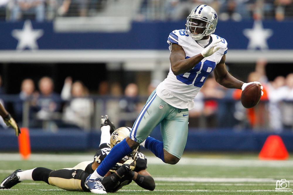Dallas Cowboys wide receiver Dez Bryant (88) slips through New Orleans Saints tackles at Cowboys Stadium in Arlington, Texas, on December 23, 2012.  (Stan Olszewski/The Dallas Morning News)