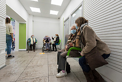© Licensed to London News Pictures. 15/01/2021. LONDON, UK.  Patients wait to receive their coronavirus vaccination at Cullimore Chemist in Edgware, north west London.  Cullimore Chemist is one of 6 community pharmacy pilot sites across the country offering coronavirus vaccinations, with 200 more to come online in the next two weeks.  Three special purpose consulting rooms have been constructed, staffed by qualified vaccinators to administer the Oxford-AstraZeneca vaccine.  Proprietor Hassan Khan expects to be able to offer 1,200 jabs per week, but the current problem is a bottleneck in vaccine supply.  Photo credit: Stephen Chung/LNP