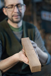 Male bow maker checking quality of wood in workshop, Bavaria, Germany