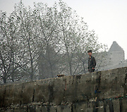 A North Korean soldier stands guard on the pier of the border town of Sunuiju Ocotber 10, 2006.  DPRK, north korea, china, dandong, border, liaoning, democratic, people's, rebiblic, of, korea, nuclear, test, rice, japan, arms, race, weapons, stalinist, communist, kin jong il