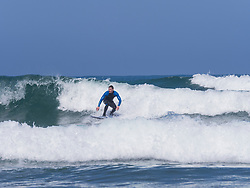Young man surfing on Sopela Beach, Biscay, Basque Country, Spain