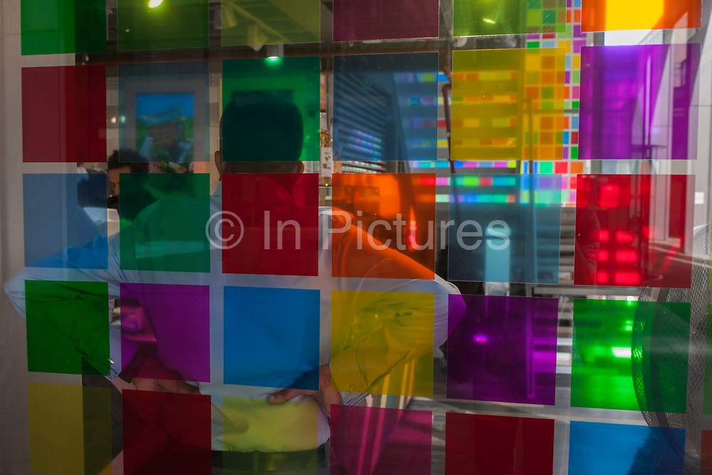 Seen through the chequered squares of a shop window, a worker on a lunch break waits to be served on 8th September 2016, in the City of London, England UK. With hands on hips he patiently awaits service during a precious time away from his desk in the heart of the capitals financial district, founded by the Romans in the first century.