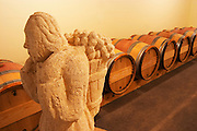 The barrel cellar for aging the wines in oak casks with  A stone sculpture in the cellar - a man carrying grapes in a basket on the back - Chateau La Grave Figeac, Saint Emilion, Bordeaux