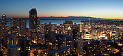 """Downtown Seattle, the Space Needle, Puget Sound and the Olympic Mountains at sunset, on July 4, 2007. Published in """"Light Travel: Photography on the Go"""" book by Tom Dempsey 2009, 2010. (Panorama stitched from 4 images; photographed by Tom Dempsey from the 33rd floor of First Hill Plaza, 1301 Spring Street, Seattle, Washington.)"""
