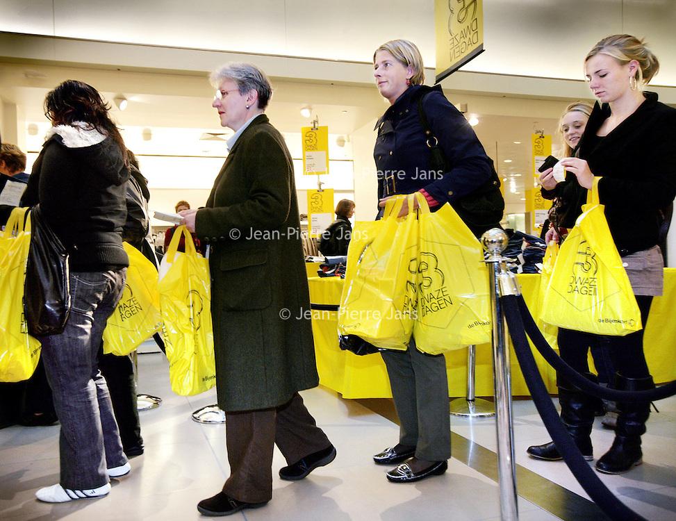 Nederland, Amsterdam , 1 oktober 2009..Bezoekers van warenhuis de Bijenkorf begeven zich met tassen vol koopjes tijdens de Drie dwaze Dagen richting de kassa. ..Three Crazy Days, annual sale of the Bijenkorf store, promoting bargains.