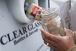 Hands putting clear glass jars into a recycling bank,