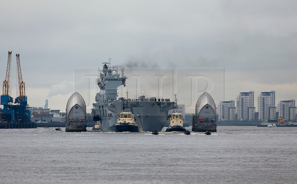 © Licensed to London News Pictures. 04/05/2012. LONDON, UK. The Royal Navy's helicopter carrier, HMS Ocean makes her way through the the Thames Barrier in London today (04/05/12). HMS Ocean has been deployed as part of an exercise involving the RAF, British Army and Royal Navy taking place across London as part of security preparations for the 2012 London Olympic Games. Photo credit: Matt Cetti-Roberts/LNP