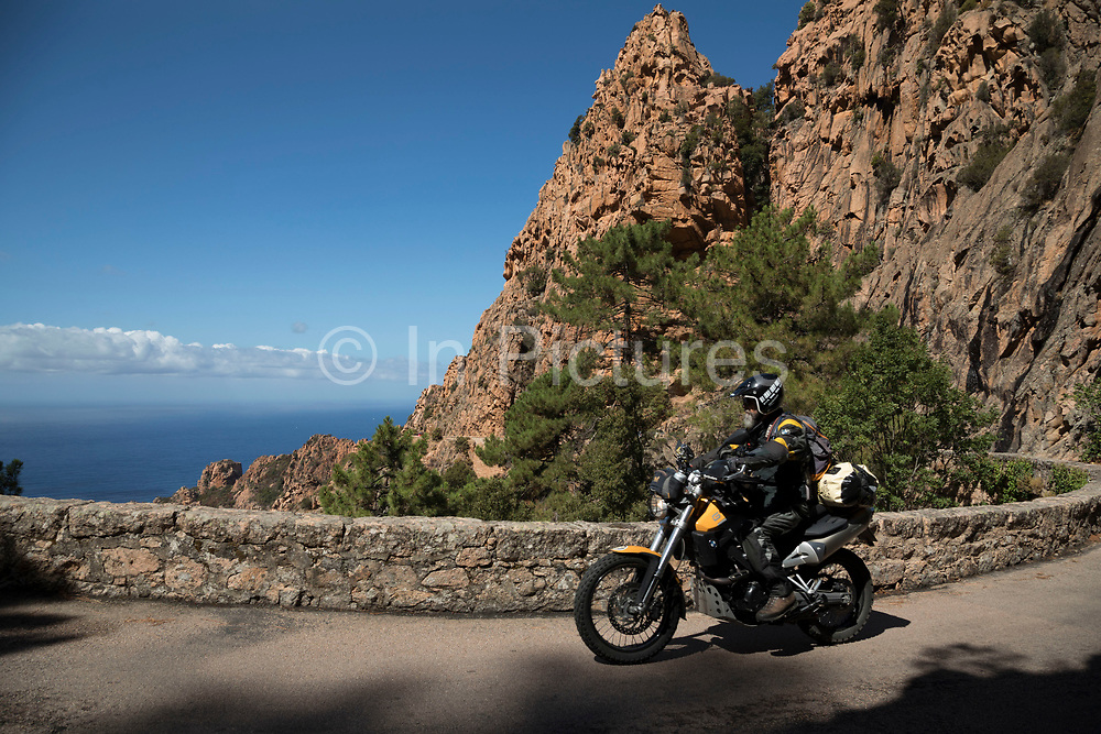 Mountain landscape of the Calanques de Piana, gold and pink coloured granite rock formations formed by wind and rain erosion creating dramatic cavities as they descend into the sea at the gulf of Porto on 11th September 2017 in Piana, Corsica, France. Corsica is an island in the Mediterranean and one of the 18 regions of France. It is located southeast of the French mainland and west of the Italian Peninsula.