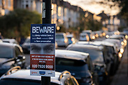 A pair of eyes watch over a suburban residential street, on a sign that warns fly-tippers not to dump rubbish on this street in south London, on 4th November 2020, in London, England.