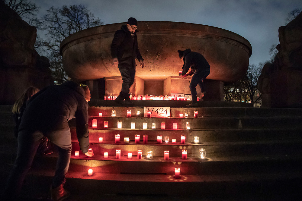 "People gather at  a makeshift memorial in Berlin, Germany, January 17,  2021. The memorial is part of the initiative  ""Corona-Tote sichtbar machen"" (lit. Make corona deaths visible) by Christian Y. Schmidt and Veronika Radulovic,  since December 6, 2020, people gather at the fountain of Arnswalder Platz every Sunday at 16:00, light candles and place placards with the current death toll reported in Germany at the time. The death toll in Germany by variouse sources revolved around 47,000."